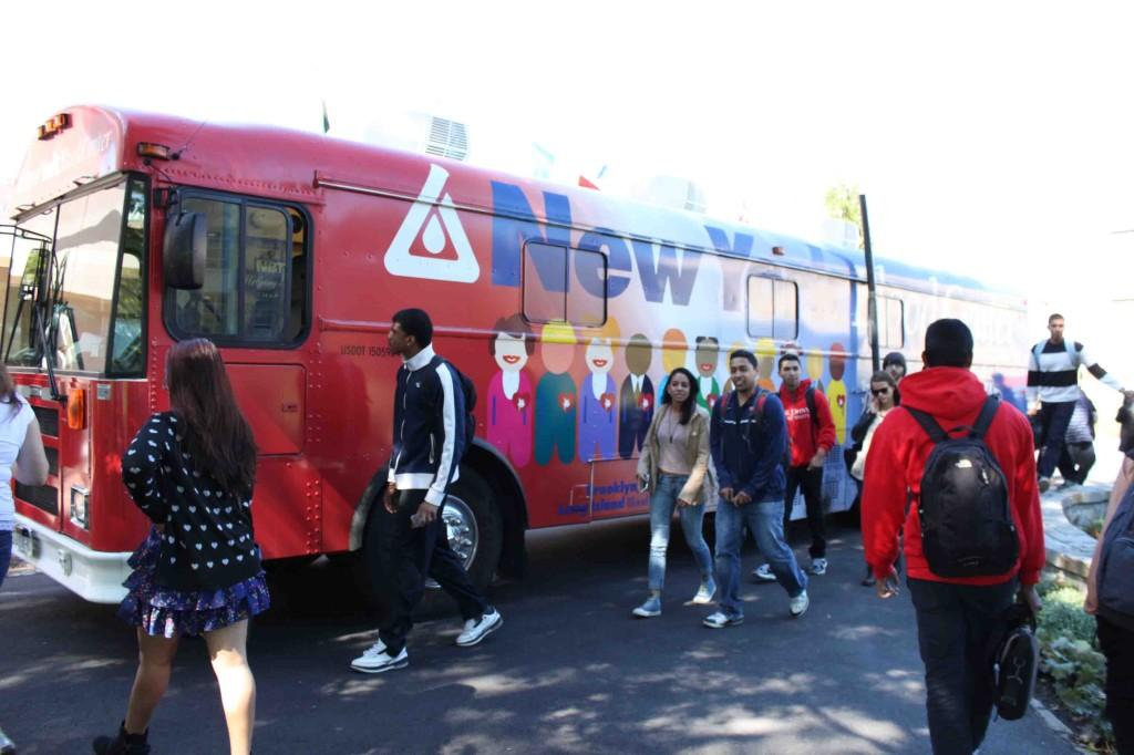 Students+walk+past+a+blood+donation+bus+stationed+by+St.+Augustine+Hall.+