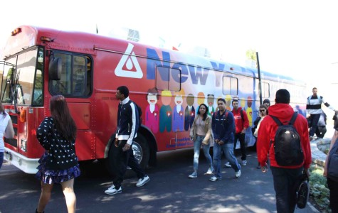Students walk past a blood donation bus stationed by St. Augustine Hall.