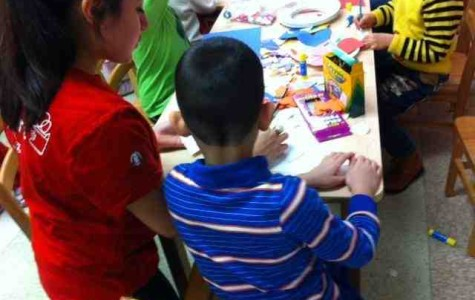 A St. John's student assists one of the kids in an arts and crafts project.