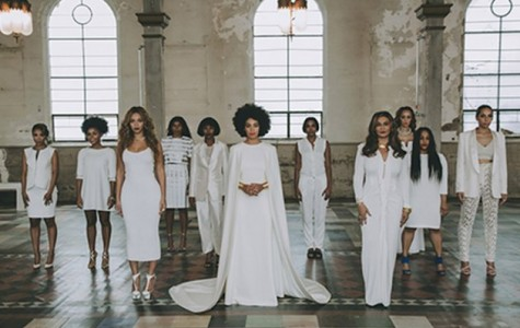 Solange Knowles decked out in a white gown with attached cape designed by Humberto Leon for Kenzo, posed alongside her bridal party in the New Orleans Museum of Art.