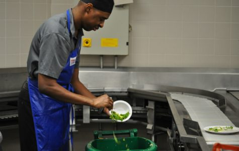 An employee behind the conveyer belt, scraping off leftover food from students' plates.