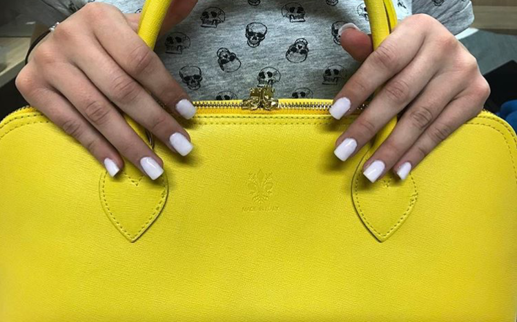 Customer displays her square-shaped full-set of nails on a purse.