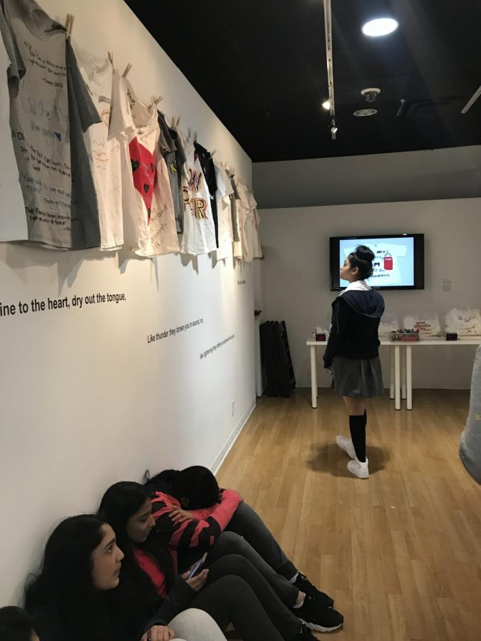 Hanging t-shirts on the walls of the gallery tell the girls' stories.