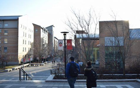 St. John's University students walk through Residence Village on a chilly spring day.