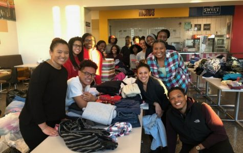 Seraiah Romero and volunteers from Eden and CSA sort clothes for easy distribution.