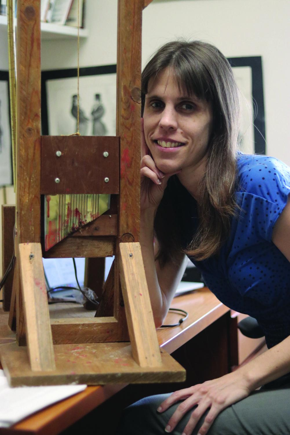 Dr. Erika Vause poses with her mini guillotine and speaks with the Torch about her history selections.