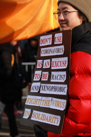 A woman carries a sign during the 2020 Lunar New Year Parade in an effort to bring awareness to the xenophobia in the United States.